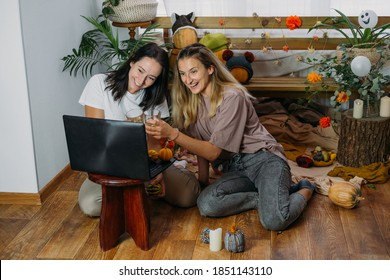 Thanksgiving online party, virtual dinner gathering. Holidays in the Time of COVID new normal, Pandemic time. Happy family, friends, two women celebrating Thanksgiving via internet near laptop