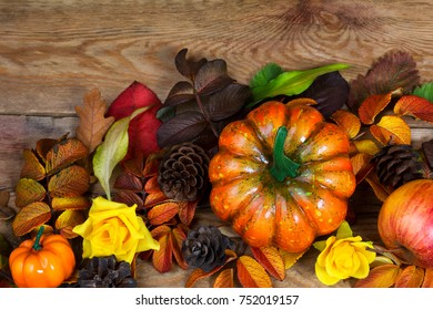 Thanksgiving orange pumpkin, apple, pine cones and yellow roses arrangement on the wooden background, top view