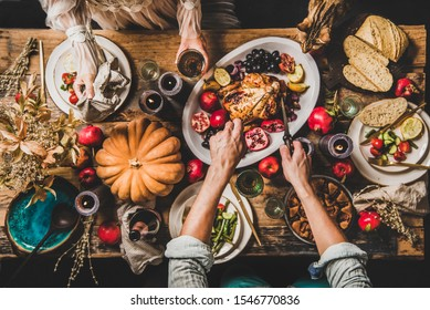 Thanksgiving party table setting. Flat-lay of whole roasted chicken, vegetables, fig pie, fruit, pumpkin, candles, tableware, eating people and tiger cat over rustic wooden table background, top view