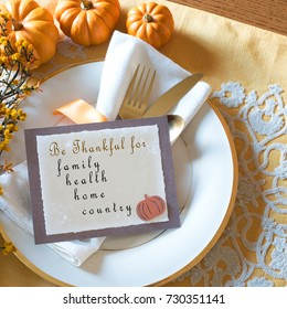 Thanksgiving Place Setting with Menu Card with Be Thankful for family, health, home, country in Text. Above View Square with silverware, pumpkins, white plate and golden tone place mat with copy space