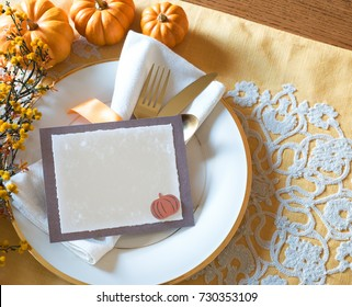 Thanksgiving Place Setting with Menu Card with Blank Menu Card for your words, text or copy.  Above View horizontal with silverware, pumpkins, white plate and golden tone table mat with copy space
