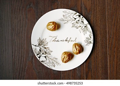 Thanksgiving Plate with Gold Acorns on Wood Table