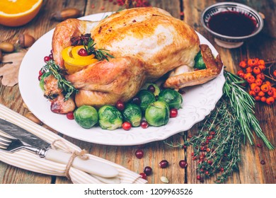 Thanksgiving roasted chicken with Brussels sprouts and spices on a rustic wooden table. Thanksgiving dinner or fall dinner concept background with autumn leaves. Thanksgiving table setting background.