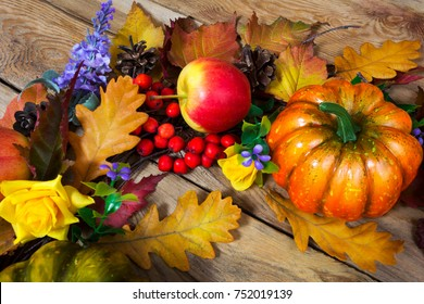 Thanksgiving rustic background with yellow rose, oak leaves, pumpkin, apple, lilac flowers and rowan berries, top view