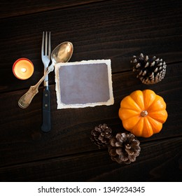 Thanksgiving Still Life Place setting with Vintage Silverware, empty card, and candle on Dark Rustic Wood Table.