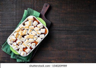 Thanksgiving sweet potato casserole with marshmallow topping, sweet thanksgiving dish on a wooden cutting board with green kitchen dish towel on a wooden table, copy space, horizontal
