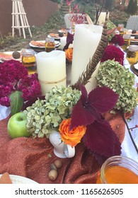 Thanksgiving table beautifully decorated with pumpkins, corn, roses, hydrangeas, candles, feathers, linens, plates, napkins, apples, and juice. Ready for a family to enjoy Thanksgiving feast together.