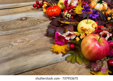 Thanksgiving table centerpiece with pumpkins, apples, fall leaves, red berries, pink and purple flowers, copy space