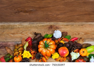 Thanksgiving table centerpiece with pumpkins, apples, pine cones, colorful fall leaves, yellow roses and white flower on the rustic wooden background, copy space