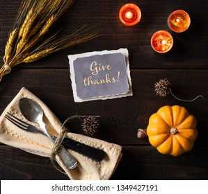 Thanksgiving Table Place Setting with Vintage Silverware, Lighted Candles, wheat and pumpkin, all on Dark Rustic Wood Table.  The card text says Give Thanks