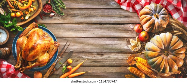 Thanksgiving table served with turkey, decorated with pumpkins and autumn leaves on rustic wooden table