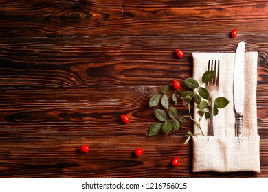 Thanksgiving table setting concept. Fork and knife with dog-rose leaves and berries on brown wooden table. November mood background with briar branches. Copy space, close up, top view, flat lay.