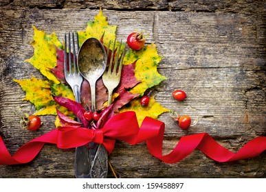 Thanksgiving table setting/ cutlery on the autumn background with  autumn leaves,ribbon on wooden abckground/Thanksgiving holidays background concept