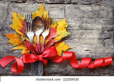 Thanksgiving table setting/ cutlery on the autumn background with autumn leaves,ribbon on wooden background/Thanksgiving holidays background concept