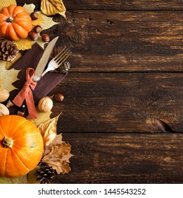 Thanksgiving Table Setting, top view, copy space. Autumnal holiday decorated table with pumpkins, cutlery, yellow leaves.