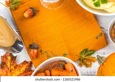 Thanksgiving table with traditional side dishes - mashed potatoes, gravy sauce and roasted carrots