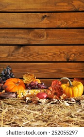 Thanksgiving - vegetable and fruits on straw in front of old weathered wooden boards