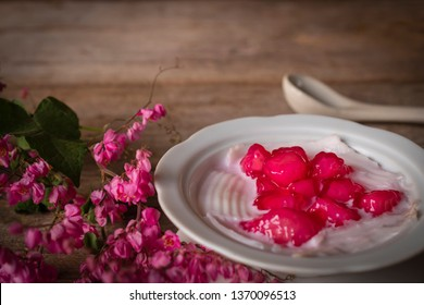 Thapthim krop, mock pomegranate seeds in coconut and syrup in the white bowl on the wood table there are flower and spoon placed around.