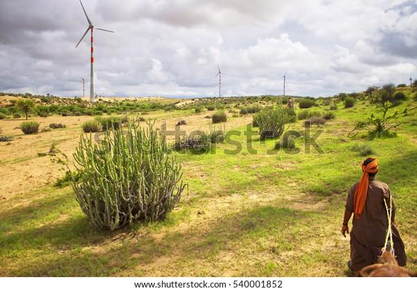 Thar desert - wind power plants and a local man leading camel caravan. India