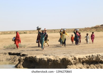 Tharparkar Sindh, Pakistan - March, 2019: Children wearing colorful dress coming to watering in the pot or filling water pots from stagnant water pond in Thar Pakistan, the area struck by drought