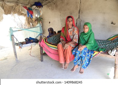 Tharparkar Sindh, Pakistan - March, 2019: Poor Women wearing Colorful clothes sitting upset with girl in a poor hut village in Thar Pakistan, it is the desert are most affected by drought in Pakistan