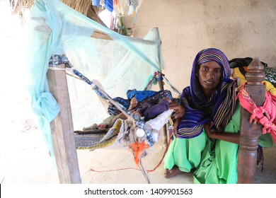 Tharparkar Sindh, Pakistan - March, 2019: Poor Women wearing Colorful clothes sitting with infant in a poor hut village in Thar Pakistan, it is the desert are most affected by drought in Pakistan