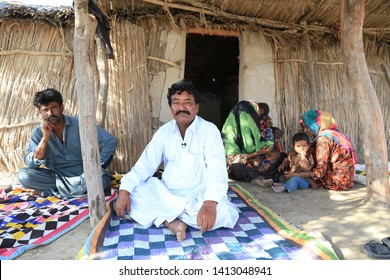Tharparkar Sindh, Pakistan - March, 2019: Poor Man sitting on ground upset with family outside his hut house village in Thar Pakistan, it is the desert are most affected by drought in Pakistan