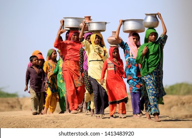 Tharparkar Sindh, Pakistan - March, 2019: Women wearing Colorful clothes walking carrying water pot on their heads in Thar Pakistan