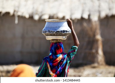 Tharparkar Sindh, Pakistan - March, 2019: View from Back Woman wearing Colorful clothes carrying water pot on her head in Thar Pakistan, it is the desert are most affected by drought in Pakistan