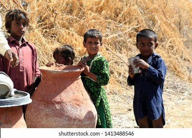 Tharparkar Sindh, Pakistan - March, 2019: Poor Children desperate to drinking water from pot in a village in Thar Pakistan, it is the desert are most affected by drought in Pakistan