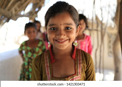 Tharparkar Sindh, Pakistan - March, 2019: Poor Girls wearing Colorful clothes smiling shying laughing under huts in a village Thar Pakistan, it is the desert are most affected by drought in Pakistan