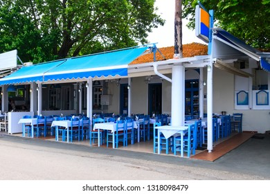 Thassos, Greece - May 5, 2018: Traditional greek open-air taverna, cafe and restaurant with blue and white chairs and tables, Greece