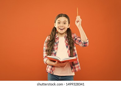 That book has given me several ideas. Little girl writing down her idea into diary. Small child pointing pen up having genius idea. Adorable schoolgirl got main idea of book.