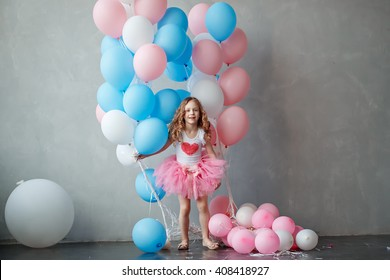 That cute little curly girl in a lush pink skirt plays with balloons. Holiday, birthday