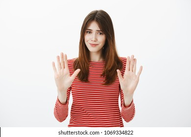 That is enough, thanks. Portrait of uncomfortable pretty brunette, raising palms in no or stop gesture, smiling awkwardly, wanting to decline offer politely, feeling insecure and nervous