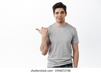 That is lame. Unimpressed and disappointed man pointing aside at bad offer, looking displeased and skeptical, standing over white background