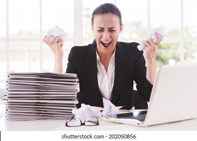 That is too much for me! Furious young woman in formalwear holding papers in hands and shouting while sitting at her working place