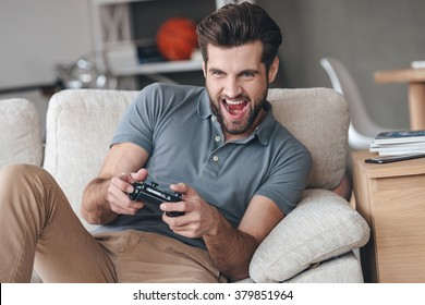 That is my best round! Excited young handsome man playing video game and keeping mouth open while sitting on the couch at home