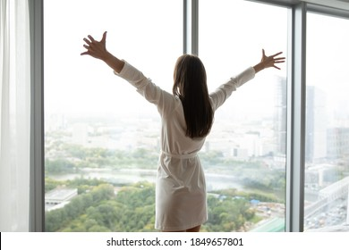 That is my world! Charming young woman in bathrobe standing at large panoramic window wall stretching hands to sides opening embraces to life enjoying splendid city panorama meeting new day, back view