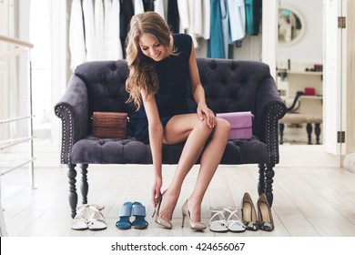 That is perfect pair! Beautiful young woman trying on high heel shoes while sitting on sofa at the shoe store