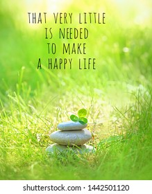 that very little is needed to make a happy life - inspiration quote. Relax still life with stacked of stone and clover leaf in summer grass. spa nature scene, soul calmness concept.