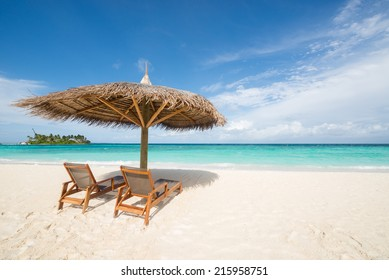Thatch umbrella and beach chair on tropical beach, Maldives
