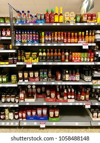 THATCHAM, BERKSHIRE - MARCH 31, 2018: Bottles of hot sauce and condiments on sale at Waitrose supermarket in Thatcham, Berkshire, UK.