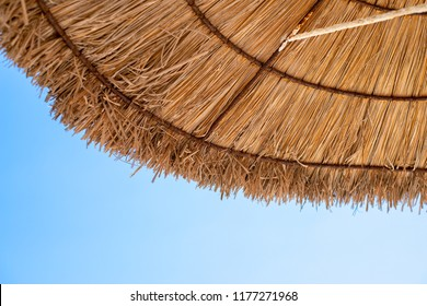 Thatched beach umbrella shot from underneath over clear blue sky