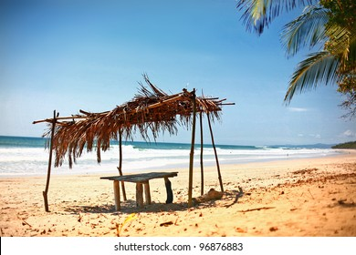 Thatched roof over beach picnic table on sandy beach with ocean waves and blue sky