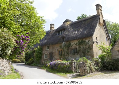 Thatched roof, stone cottage with flowering gardens,  by a country road, on a summer sunny day .