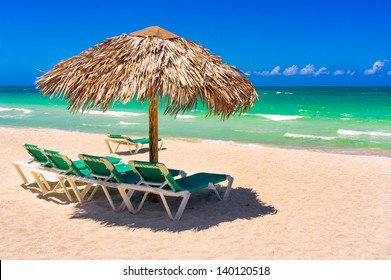 Thatched umbrellas and beach beds on a tropical beach in Cuba