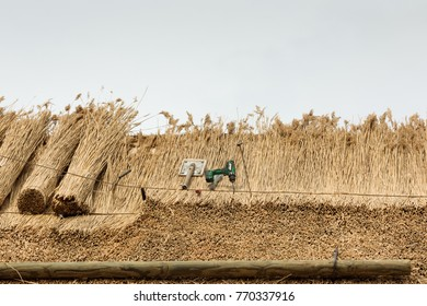 Thatcher thatching a roof of a house with new straw.Thatched roof of a home