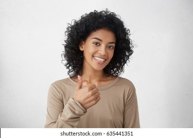 That's way all better. Cheerful enthusiastic beautiful young mixed race woman with curly hair showing thumbs up gesture to camera, expression her like and approval of idea or project, smiling broadly