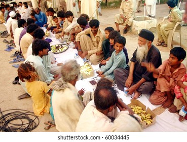 THATTA, PAKISTAN - AUG 29: Renowned Social Worker Abdul Sattar Edhi (2nd-R) sits along with flood affected people as they prepare Iftari on August 29, 2010 in Thatta.